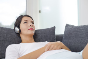 Beautiful serene young woman relaxing with a sensual glint in her eyes listening to music on a set of headphones lying on her back on a sofa in casual shorts